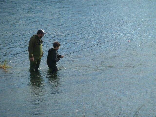 Boy playing a fish guided by his dad